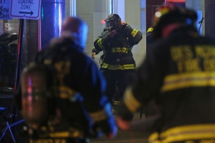 Members of the Des Moines Fire Department prepare to go back inside the Elliott Apartments where a fire was reported late on Wednesday night, June 15, 2016, on Fourth Street downtown. The fire department worked late in to the night and next morning to make sure the fire did not spread.