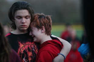 Logan Tedder and RyAnne Borcherding, both of Mason City embrace during a vigil on Tuesday, April 11, 2017, at Georgia Hanford Park, honoring the five people killed in a car accident in Mason City on Monday.
