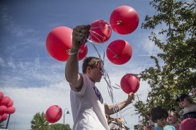Dylan Smith, of Urbandale, hands out balloons for the Urbandale Community Action Network during the city's 4th of July parade on Tuesday, July 4, 2017, in Urbandale. The parade's theme was a celebration of the city's 100th anniversary.